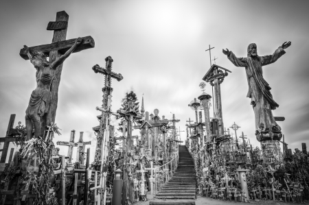 Hill of crosses in Siauliai, the city of Lithuania. Old stairway goes to gray sky. Stairs lead to the top of hill. Crosses and statues of saints near. Sun shines weakly, so place looks mysterious.