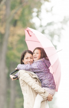 Beautiful mother embracing daughter under umbrella  Smiling woman and girl in rainy weather  Portrait of happy mom and kid  Young parent with child walking in park in autumn  Family outdoor activity の写真素材