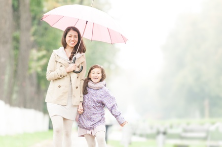 Young beautiful woman with pretty little daughter walking together in park under umbrella  Mother and daughter holding hands  Friendly family being happy and cheerful  Family walk outdoor in rain の写真素材