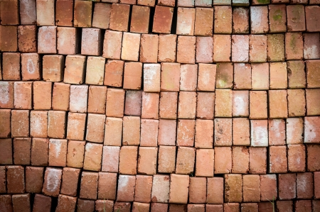 New red brick pavers stacked in rows like wall  Store of bricks ready for building or sale  Construction materials and outdoor storage  Abstract background