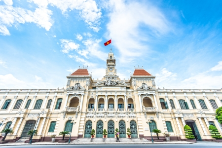 French style of building in Vietnam, Asia. Beautiful Ho Chi Minh City Hall. Facade of house with ornate design. Red flag contrasts with blue sky and clouds. Tourist attraction, famous landmark.のeditorial素材
