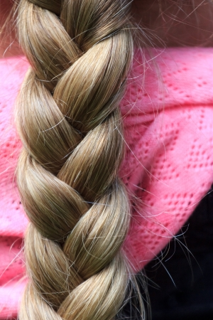 A blond long and thick braid of a woman