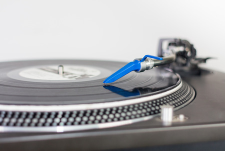 Closeup of a DJ needle on black vinyl record on a classic turntable