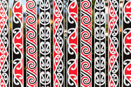 Photo pour An ornate fence with a typical Maori pattern in red, white and black in Rotorua, New Zealand - image libre de droit