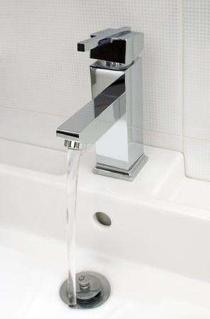 Closeup of modern bathroom tap, flowing tap water