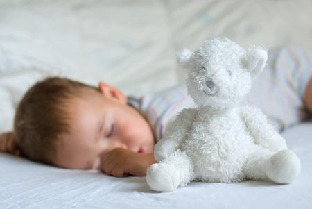 Sweet dream - white bear against sleeping little boy