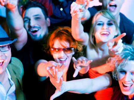 Crowd cheering - their rock idol or simply having fun in a club or disco party (focus on hands!)
