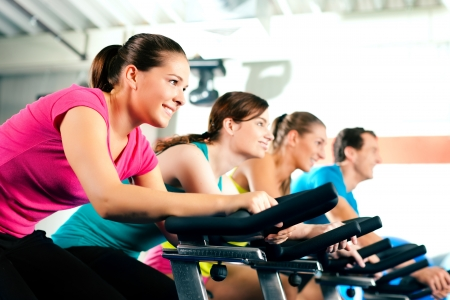 Foto de Group of four people spinning in the gym, exercising their legs doing cardio training - Imagen libre de derechos