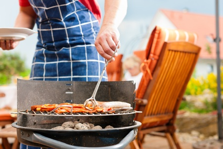 Happy family having a barbecue in summer; father stands next to the fire