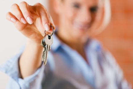 Photo pour Woman is giving the keys to an apartment to some clients focus on the keys - image libre de droit