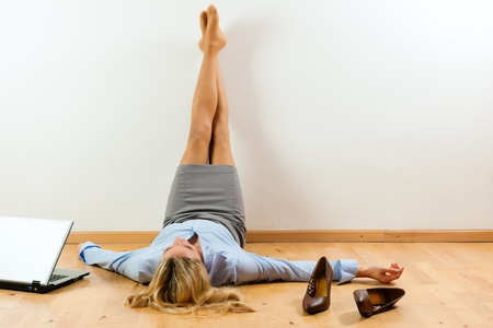 Photo pour Businesswoman is lying on the floor at home relaxing - image libre de droit