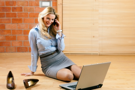 Photo pour Business woman working at home with her laptop on the floor and makes a phone call - image libre de droit