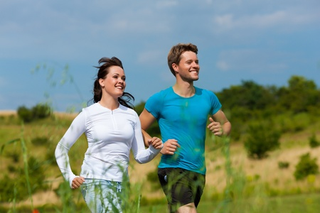 Young fitness couple doing sports outdoors; jogging on a green meadow in summer under the sky with lots of clouds