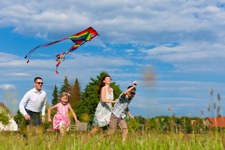 Photo pour Happy family - mother, father, children - running over a green meadow in summer; they fly a kite - image libre de droit