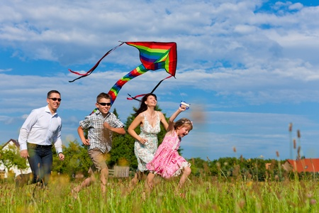 Foto de Happy family - mother, father, children - running over a green meadow in summer; they fly a kite - Imagen libre de derechos