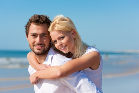 Couple in love - Caucasian man having his woman piggyback on his back under a blue sky on a beach