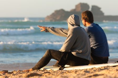 Photo pour Two surfers sitting on their surf boards on the beach discussing the waves - image libre de droit