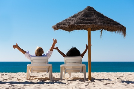 Photo for Couple sitting in sun chairs under an parasol sunshade on a beach stretching arms, feeling free - Royalty Free Image
