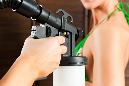Beautician (only hands to be seen) with airbrush-pistol and client in a cosmetic studio doing bronzing