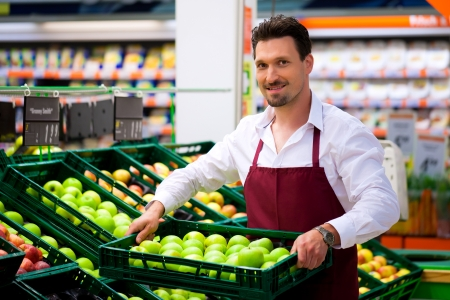 Photo for Man in supermarket as shop assistant; he brings some boxes with apples - Royalty Free Image