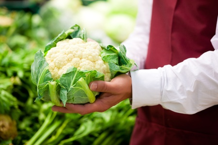 Man – only hands to be seen - in supermarket as shop assistant; he is carrying a cauliflower