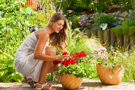 Gardening in summer - happy woman with flowers and hat in her garden