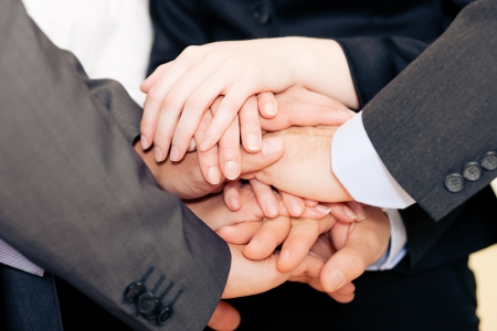 Businesspeople stacking their hands together - a strong symbol for their willingness and determination to reach a shared goal