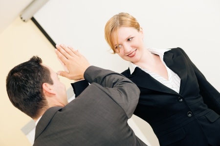 Two people in Business giving each other a high five for a successful transaction