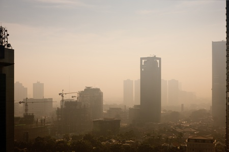 High rise building at sunrise – in a polluted city, the smog dampens color and makes the air semi-opaque