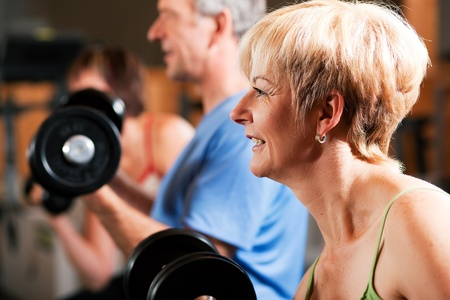 Senior people in a gym exercising with weights