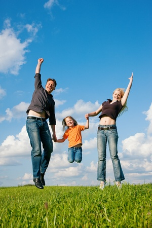 Photo pour Family - mother, father, child - running over the grass of a green meadow at a late summer afternoon - image libre de droit