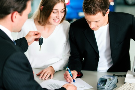 Sales situation in a car dealership, the young couple is signing the sales contract and gets the key for the new car