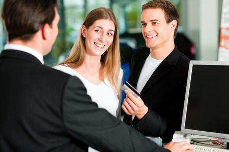 Sales situation in a car dealership, the young couple is giving the credit card to pay for the new car