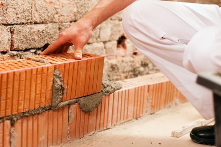 bricklayer laying bricks to make a wall, he is putting grout on top of a brick