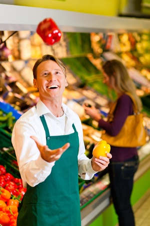 Shop assistant in a supermarket at the vegetable shelf; he is tossing a bell pepper