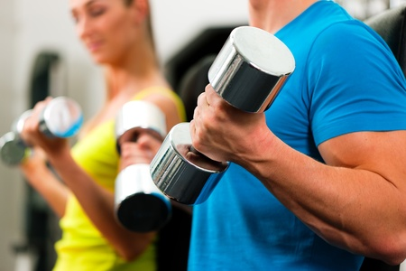 couple in the gym, rivaling each other, exercising with dumbbells