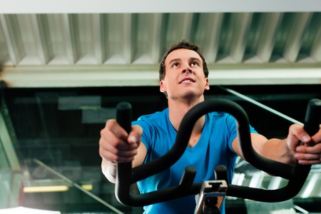 Man spinning in the gym, exercising his legs doing cardio training on bicycle