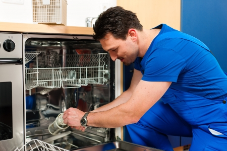 Photo pour Technician or plumber repairing the dishwasher in a household - image libre de droit