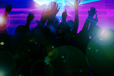 Photo pour Silhouettes of dancing people having a celebration in a disco club, the light show is sending laser beams through the backlit scene - beware: very psychedelic forms and colors - image libre de droit