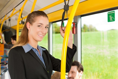 Female passenger in a bus; presumably she is heading home