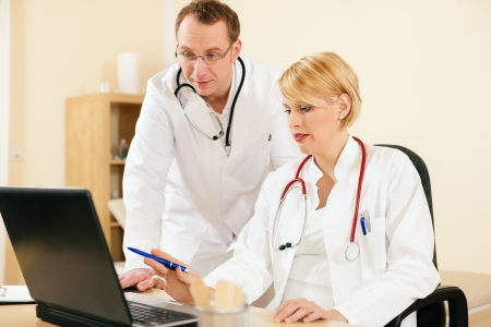Two doctors - male and female - discussing documents in their practice, test reports or maybe administrative or financial stuff