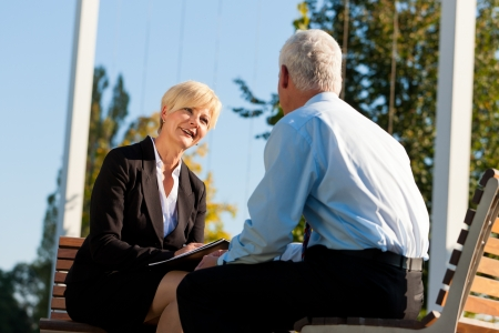 Coaching outdoors - a man and a woman have a coaching discussion