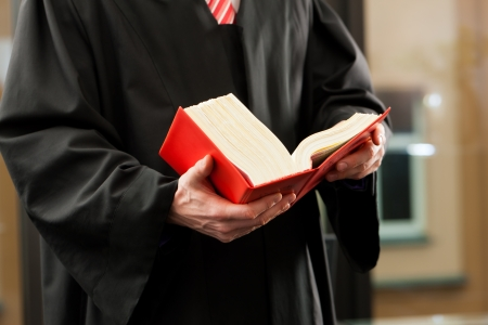 Lawyer with civil law code in a court room, close-up, only torso to be seen
