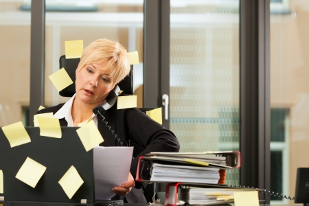 A woman has stress in the office - multitasking and time management