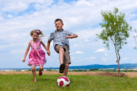 Siblings - son and daughter - playing soccer in the garden
