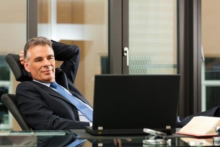 Photo pour Business - mature boss contemplating in his office - image libre de droit