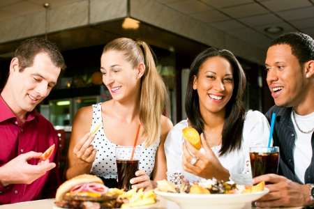 Photo pour Friends - one couple is African American - eating hamburger and drinking soda in a fast food diner; focus on the meal - image libre de droit