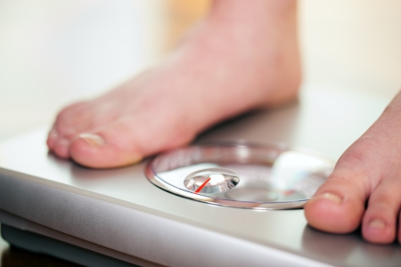 Foto de Woman (only feet to be seen) standing on bathroom scale measuring her weight controlling her dieting results  - Imagen libre de derechos