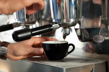Barista prepares cappuccino in his coffeeshop; close-up