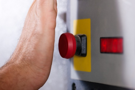Photo pour Man is shutting off a machine with the emergency button - probably in a case of danger - image libre de droit